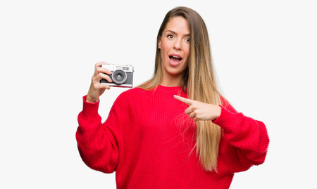 Beautiful young woman holding vintage camera very happy pointing with hand and finger