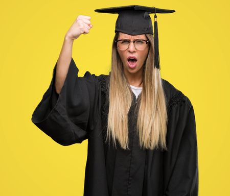 Beautiful young woman wearing glasses and graduation robe annoyed and frustrated shouting with anger, crazy and yelling with raised hand, anger concept
