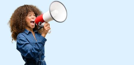 Die Afroamerikanerin, die den blauen Overall trägt, kommuniziert laut schreiend mit einem Megaphon und drückt Erfolg und positives Konzept, Idee für Marketing oder Verkauf aus Standard-Bild