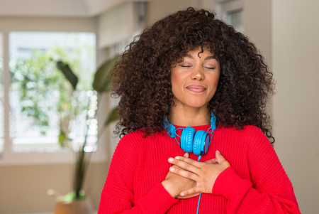 African american woman wearing headphones smiling with hands on chest with closed eyes and grateful gesture on face. Health concept.