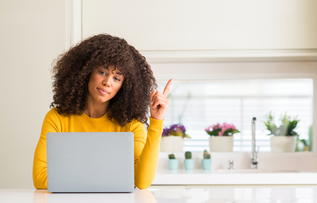 African american woman using computer laptop at kitchen very happy pointing with hand and finger to the side Imagens