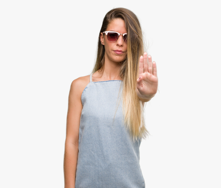 Beautiful young woman wearing sunglasses and denim dress with open hand doing stop sign with serious and confident expression, defense gesture