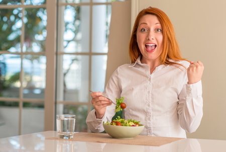 Redhead woman eating fresh green salad at home screaming proud and celebrating victory and success very excited, cheering emotion Stock Photo