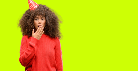 African american woman celebrates birthday cover mouth with hand shocked with shame for mistake, expression of fear, scared in silence, secret concept Stock Photo