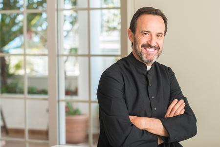 Uomo sacerdote cristiano con una faccia felice in piedi e sorridente con un sorriso fiducioso che mostra i denti