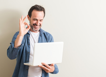 Senior man using laptop computer doing ok sign with fingers, excellent symbol