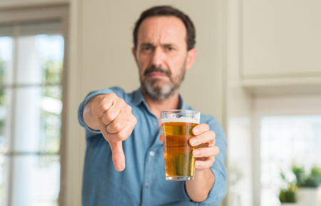 Middle age man drinking beer with angry face, negative sign showing dislike with thumbs down, rejection concept Stock fotó