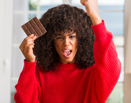 African american woman eating chocolate bar at home annoyed and frustrated shouting with anger, crazy and yelling with raised hand, anger concept