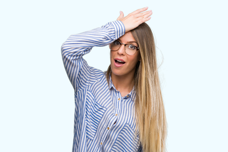 Beautiful young woman wearing elegant shirt and glasses surprised with hand on head for mistake, remember error. Forgot, bad memory concept. Stock Photo