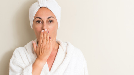 Beautiful middle age woman, wet hair wearing a towel cover mouth with hand shocked with shame for mistake, expression of fear, scared in silence, secret concept 스톡 콘텐츠