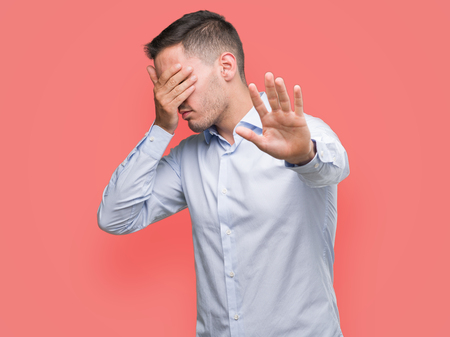 Handsome young businessman covering eyes with hands and doing stop gesture with sad and fear expression. Embarrassed and negative concept.