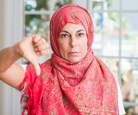 Middle aged muslim woman wearing hijab with angry face, negative sign showing dislike with thumbs down, rejection concept Reklamní fotografie
