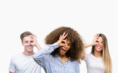Group of young people over white background with happy face smiling doing ok sign with hand on eye looking through fingers Stock Photo