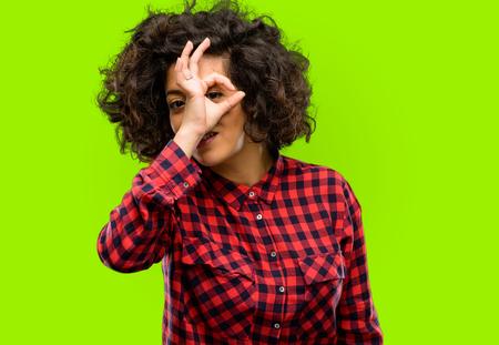 Beautiful arab woman looking at camera through fingers in ok gesture. Imitating binoculars, beautiful eyes and smile