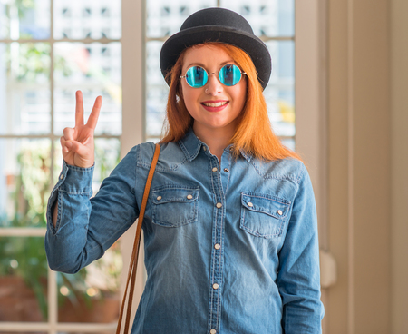 Stylish redhead woman wearing bowler hat and sunglasses showing and pointing up with fingers number two while smiling confident and happy. Stock Photo