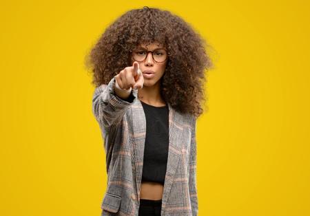 African american woman wearing a jacket pointing with finger to the camera and to you, hand sign, positive and confident gesture from the front