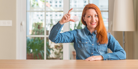 Redhead woman at home smiling and confident gesturing with hand doing size sign with fingers while looking and the camera. Measure concept.