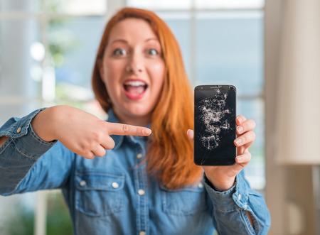 Redhead woman holding broken smartphone very happy pointing with hand and finger