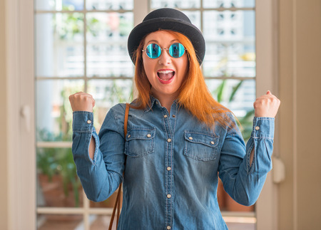 Stylish redhead woman wearing bowler hat and sunglasses celebrating surprised and amazed for success with arms raised and open eyes. Winner concept.