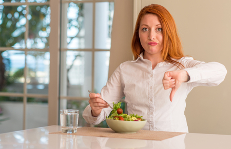 Redhead woman eating fresh green salad at home with angry face, negative sign showing dislike with thumbs down, rejection concept