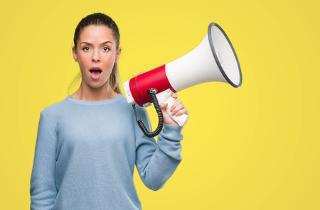 Beautiful young woman holding megaphone scared in shock with a surprise face, afraid and excited with fear expression Stock Photo
