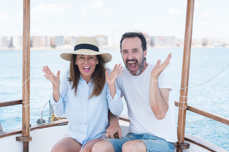 Middle age couple traveling on sailboat very happy and excited, winner expression celebrating victory screaming with big smile and raised hands Stok Fotoğraf
