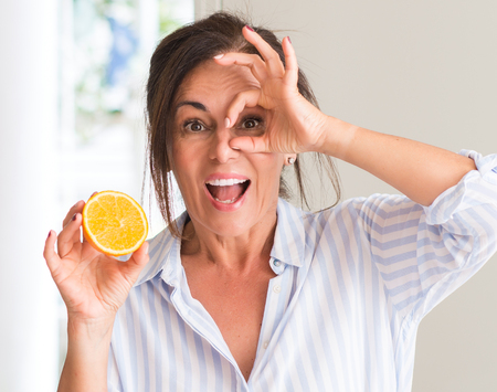 Middle aged woman holding orange fruit with happy face smiling doing ok sign with hand on eye looking through fingers