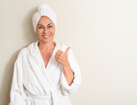 Beautiful middle age woman, wet hair wearing a towel happy with big smile doing ok sign, thumb up with fingers, excellent sign 스톡 콘텐츠
