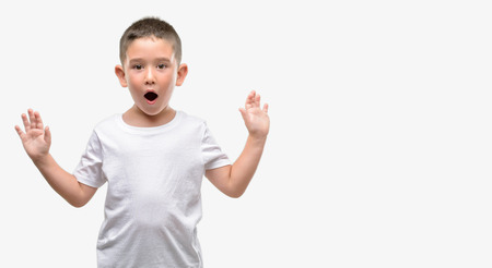 Dark haired little child scared in shock with a surprise face, afraid and excited with fear expression Archivio Fotografico