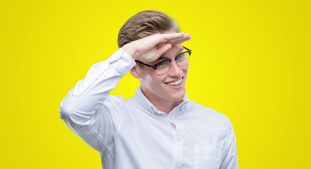 Young handsome blond man very happy and smiling looking far away with hand over head. Searching concept.