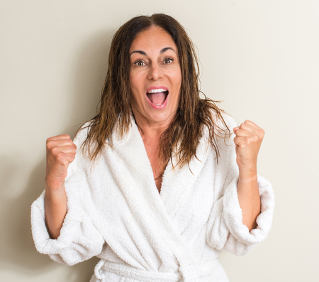 Beautiful middle age woman, wet hair wearing a towel screaming proud and celebrating victory and success very excited, cheering emotion