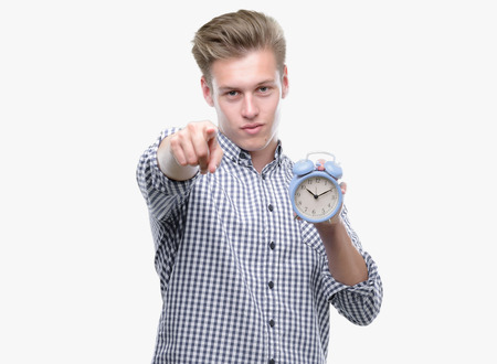 Young handsome blond man holding alarm clock pointing with finger to the camera and to you, hand sign, positive and confident gesture from the front Stock fotó