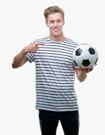Young handsome blond man holding soccer ball very happy pointing with hand and finger Фото со стока