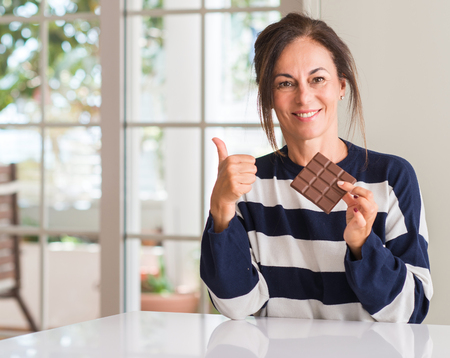 Middle aged woman eating chocolate bar happy with big smile doing ok sign, thumb up with fingers, excellent sign