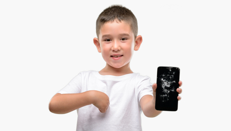 Dark haired little child holding broken smartphone with surprise face pointing finger to himself