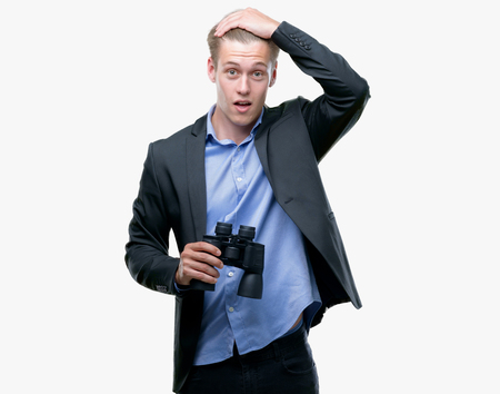 Young handsome blond man looking through binoculars stressed with hand on head, shocked with shame and surprise face, angry and frustrated. Fear and upset for mistake.