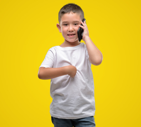 Dark haired little child using a smartphone with surprise face pointing finger to himself