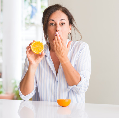 Middle aged woman holding orange fruit cover mouth with hand shocked with shame for mistake, expression of fear, scared in silence, secret concept