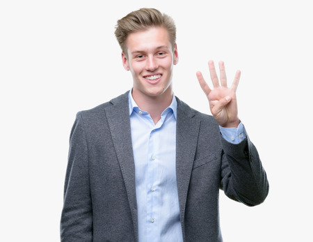 Young handsome blond business man showing and pointing up with fingers number four while smiling confident and happy.