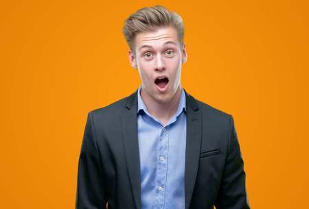 Young handsome blond business man scared in shock with a surprise face, afraid and excited with fear expression