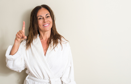 Beautiful middle age woman, wet hair wearing a towel surprised with an idea or question pointing finger with happy face, number one