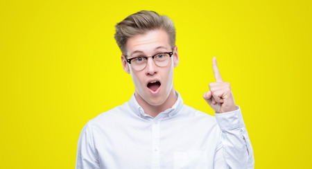 Young handsome blond man pointing finger up with successful idea. Exited and happy. Number one. Фото со стока