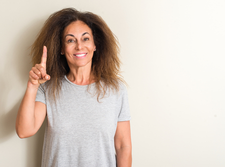 Curled hair brazilian woman surprised with an idea or question pointing finger with happy face, number one Archivio Fotografico