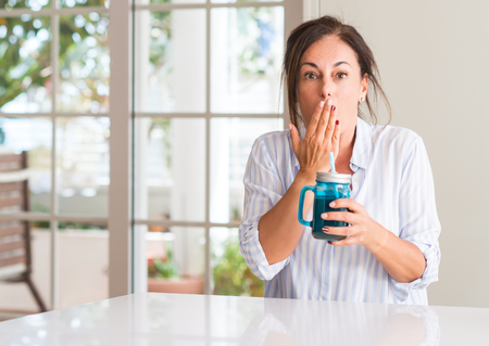 Middle aged woman drinking milk shake in a glass cover mouth with hand shocked with shame for mistake, expression of fear, scared in silence, secret concept Фото со стока