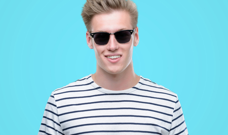 Young handsome blond man wearing sunglasess with a happy face standing and smiling with a confident smile showing teeth