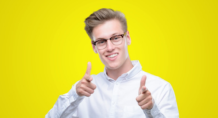 Young handsome blond man pointing fingers to camera with happy and funny face. Good energy and vibes.