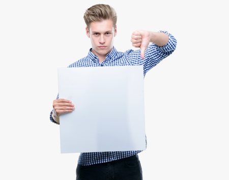 Young handsome blond man holding a banner with angry face, negative sign showing dislike with thumbs down, rejection concept Archivio Fotografico