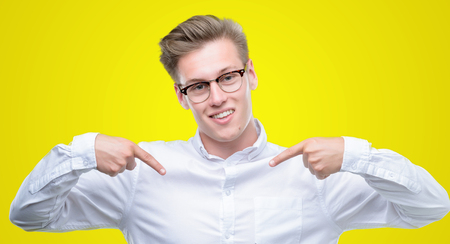 Young handsome blond man looking confident with smile on face, pointing oneself with fingers proud and happy. Фото со стока