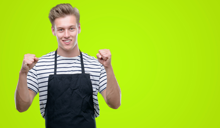 Young handsome blond man wearing apron screaming proud and celebrating victory and success very excited, cheering emotion Archivio Fotografico