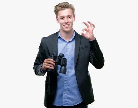 Young handsome blond man looking through binoculars doing ok sign with fingers, excellent symbol